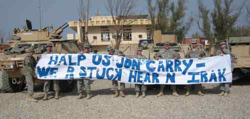 Troops in Iraq holding a poorly written banner.